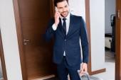 glücklicher Geschäftsmann, der im Hotelzimmer mit dem Smartphone spricht