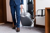 Ausgeschnittene Ansicht eines Mannes in offizieller Kleidung, der mit Gepäck das Hotelzimmer betritt