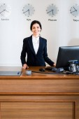 cheerful brunette receptionist in formal wear standing near computer monitor in hotel