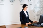 happy brunette receptionist in formal wear standing near computer monitor in hotel