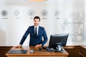 Photo cheerful receptionist in suit standing near computer monitor in hotel
