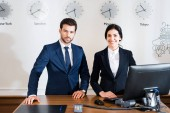 cheerful woman near serious receptionist in suit standing at reception desk