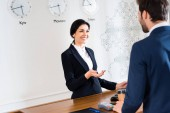 Photo selective focus of happy receptionist gesturing while looking at man