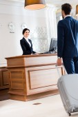 Photo selective focus of attractive receptionist looking at businessman walking with luggage