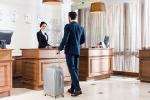 attractive receptionist looking at businessman with luggage