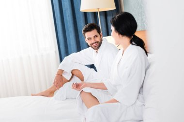 Selective focus of cheerful man looking at woman in hotel room stock vector