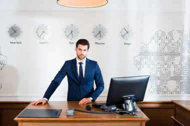handsome receptionist standing at reception desk in hotel