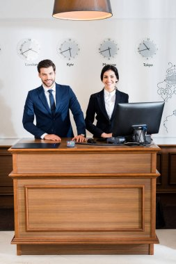 Cheerful receptionists in formal wear standing at reception desk stock vector