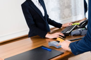 cropped view of man paying while holding credit card in hotel