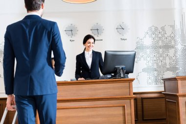 Back view of businessman near cheerful receptionist looking at computer monitor stock vector