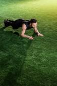 pohledný atletický muž na zelené trávě