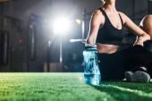 oříznutý pohled atletické ženy sedící na trávě a držící sportovní láhev