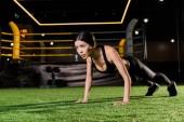 vonzó és sportos nő csinál sajtó felemel a zöld fű
