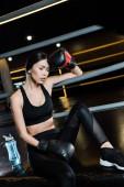 woman in boxing gloves touching head near sport bottle in gym