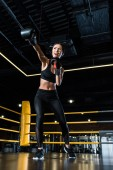 Photo low angle view of confident woman boxing while standing in boxing gloves in gym