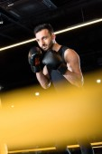 Photo selective focus of confident man boxing in sports center