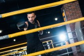 Photo selective focus of strong man in boxing gloves working out in gym