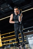 Photo low angle view of handsome man standing in boxing gloves in gym