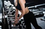 cropped view of athletic young woman taking dumbbells in gym