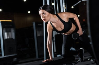 low angle view of strong and beautiful woman working out with dumbbell in gym