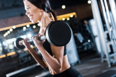 selective focus of young woman working out with heavy barbell in gym
