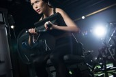 low angle view of sportswoman exercising on training apparatus in gym
