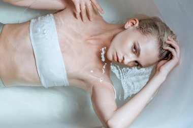 top view of seductive woman lying in clear water in bathtub