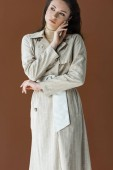 stylish woman in trendy trench coat isolated on brown, holding hand near face