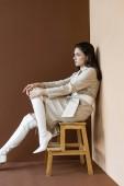 oldalnézetből gyönyörű és divatos nő ül lépcsőn, elnéz