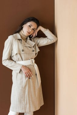 Stylish woman in trendy trench coat standing on brown background, looking at camera stock vector