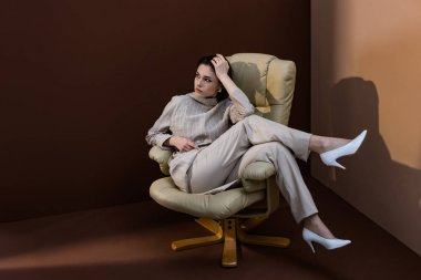 trendy model sitting on armchair, crossing legs, looking away
