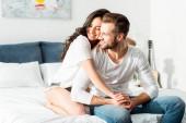 šťastný usměvavý pár objímající v posteli ráno