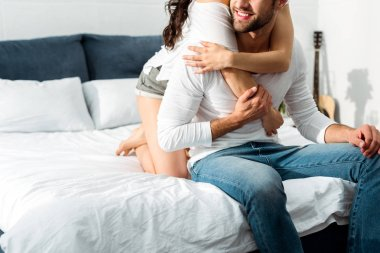cropped view of young couple hugging in bed at morning