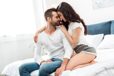 boyfriend and girlfriend gently embracing in bed at morning