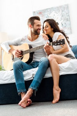 smiling man playing acoustic guitar while looking at happy woman in bed