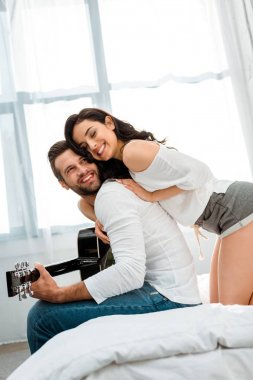 happy boyfriend playing acoustic guitar near smiling girlfriend in bed