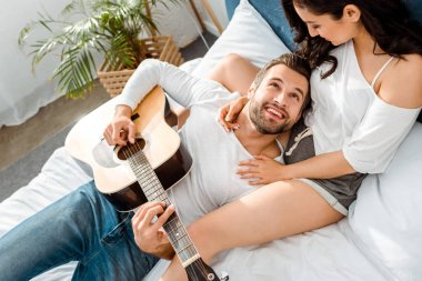overhead view of smiling man lying with acoustic guitar and looking at woman in bed