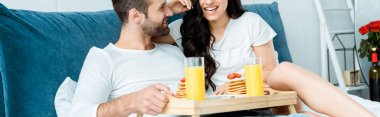 Cropped view of happy couple lying in bed and having breakfast together, panoramic shot stock vector