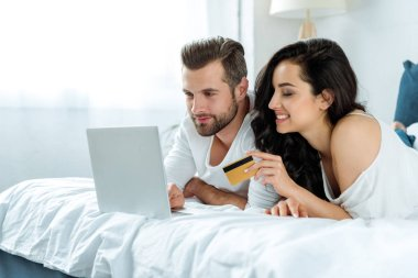 happy couple using laptop together and lying in bed while woman holding credit card, illustrative editorial