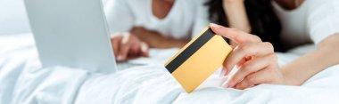 Selective focus of woman holding credit card near man with laptop, panoramic shot stock vector