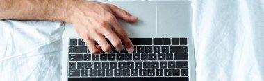 panoramic shot of man typing on laptop keyboard, illustrative editorial