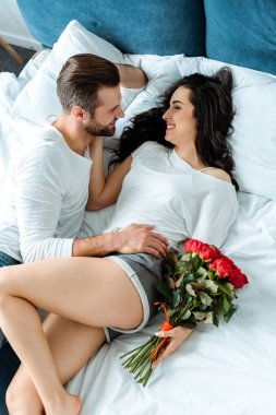 overhead view of happy couple lying in bed with bouquet of red roses
