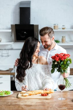 happy man gifting bouquet of red roses to woman at kitchen