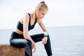 Müde blonde Sportlerin sitzt auf Stein am Meer und schaut Fitness-Tracker an