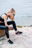 Erschöpfte blonde junge Sportlerin sitzt auf Stein am Meer