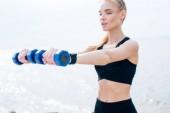 selektiven Fokus der blonden athletischen Mädchen beim Training mit Hanteln in der Nähe des Meeres