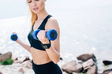 cropped view of blonde young woman exercising with blue dumbbells near sea