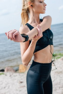 selective focus of blonde athletic girl stretching and listening music near sea