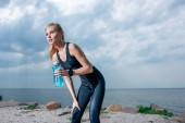 attractive and athletic woman holding sport bottle and standing near sea