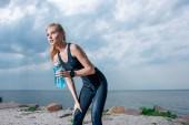 attraktive und athletische Frau mit Sportflasche in der Hand und am Meer stehend